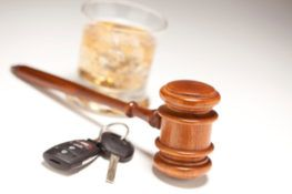 gavel, car key and alcohol