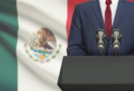 body of new mexican president at podium in front of mexico's flag
