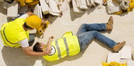hurt construction worker laying on the floor and being assisted by a coworker