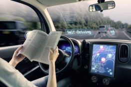 self-driving car with driver pictured reading a book
