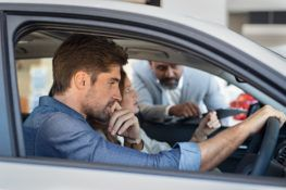 car salesman showing customer new car features