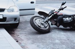 wrecked motorcycle hit by grey car parked on curb
