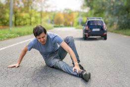 Hit and run concept. Injured man on road in front of a car