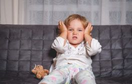 toddler boy holding ears sitting on couch with a teddy bear