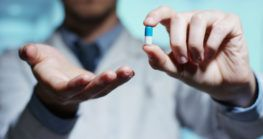 hand of a hospital medical expert shows the pill to be taken to his patient. concept of generical pills H