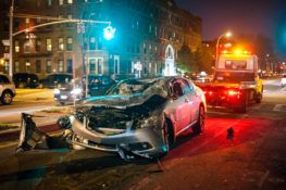 wrecked silver car at intersection nighttime