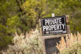 private property sign on wood pole in brush