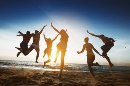 group of friends jumping in air on beach sunset