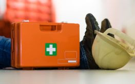 First aid medkit next to injured construction worker