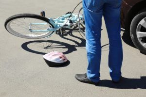 man checking damages to his bicycle after a McAlester accident.