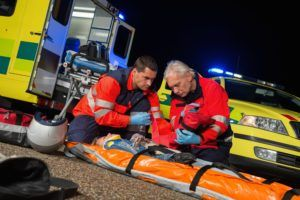 Paramedics giving first-aid to injured motorbike woman driver at night.