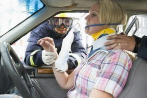 Firefighters helping an injured woman in a car.