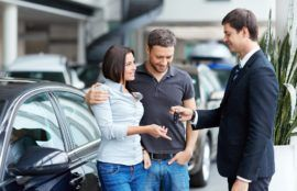 Couple receiving the car key in car rental services.