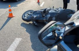 Broken motorcycle on the side of the road after an accident.