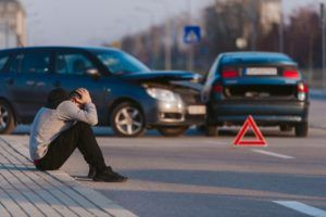 A man is looking desperate after two cars crashing on the road by his fault.