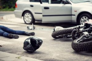 motorcyclist on the ground with bike and helmet after a motorcycle accident