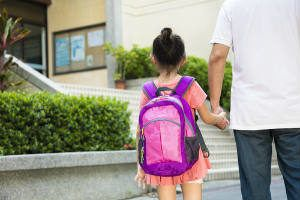 a father walking daughter to school