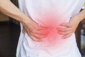woman expresses back pain due to degenerative disc disease