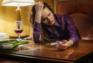 woman holding drugs and alcohol suffering from depression after being hurt at work