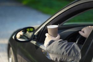 Man on his way to work driving holding a cup of coffee
