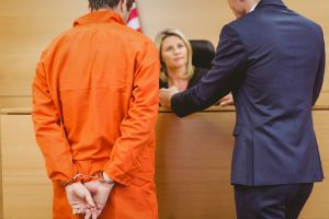 A New Jersey drug crimes lawyer approaches the bench with a client.