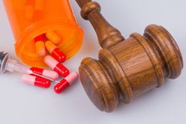 Pills and a gavel to represent drug crime law in New Jersey.