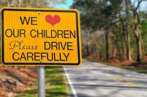 We love our children please drive carefully sign on road