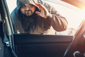 Car thief in hood looks inside car through window to show vehicle theft prevention