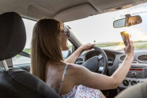 Young woman driving while using Snapchat to take photo while driving
