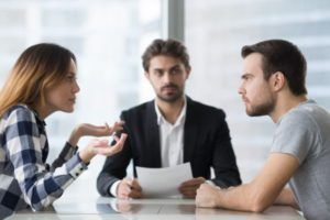 Recently divorced couple arguing over lottery winnings with lawyer present holding paperwork