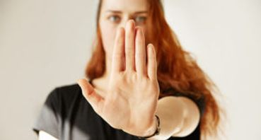 a woman placing her left hand on a stop or restrain action