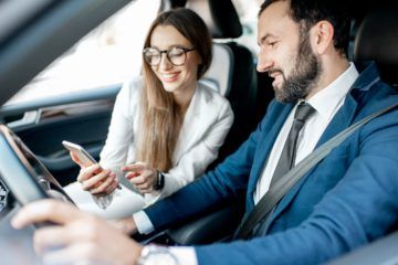 Businessman and woman dressed in the suits talking together while driving a luxury car in the city.