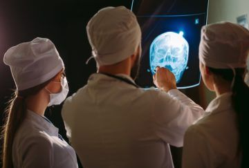 Doctors examining a patient's x-ray.