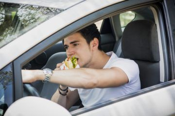 Young man is eating burger while driving.