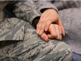 2 people in military holding hands