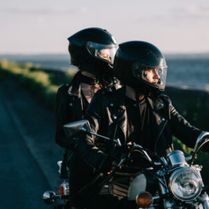 couple bikers with helmets riding classical motorcycle