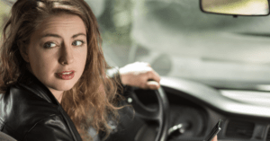 young woman distracted while driving car