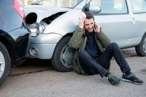 Man calling for first aid after car accident.