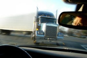 Close call imminent crash accident with a tractor trailer truck viewed from inside a car with scared driver face in rear view mirror.