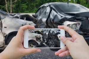 A man is taking photos of a Houston car accident.
