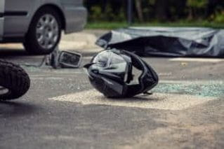 Black motorcycle helmet on the ground after a motorcycle accident