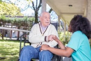 Nurse helping elder patient in hospital garden.