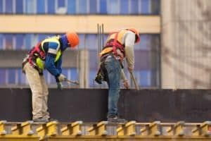 Two Alabama workers with hammers build scaffolding at a construction site.