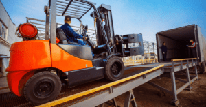 Forklift is putting cargo from warehouse to truck outdoors.