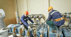 Electricians at huge power industrial transformer installation.