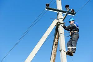 Lineman climbing work on electric post power pole.