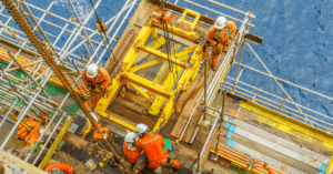 Offshore workers with full Personal Protective Equipment (PPE) performing maintenance.