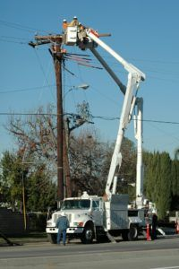Utility workers using bucket truck.