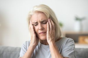 Elderly woman in Alabama suffering from a headache due to Elmiron.