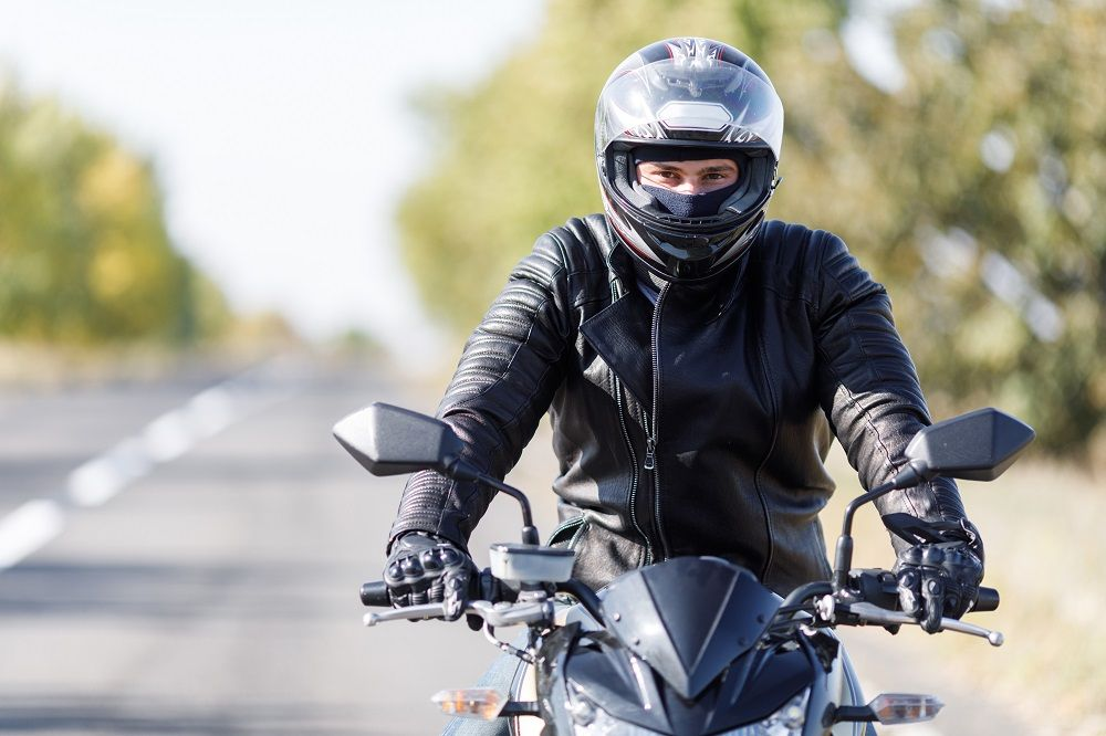 Motorcycle rider wearing helmet for safety.